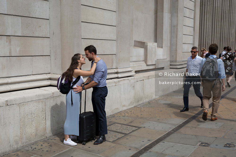 As heatwave temperatures climb to record levels - the hottest day of the year so far - a couple beneath the pillars of the Bank of England kiss in the City of London (the capital's financial district aka the Square Mile), on 25th July 2019, in London, England.