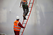 Workers working on Tower Bridge use a ladder. Health and Safety regulations may apply here.