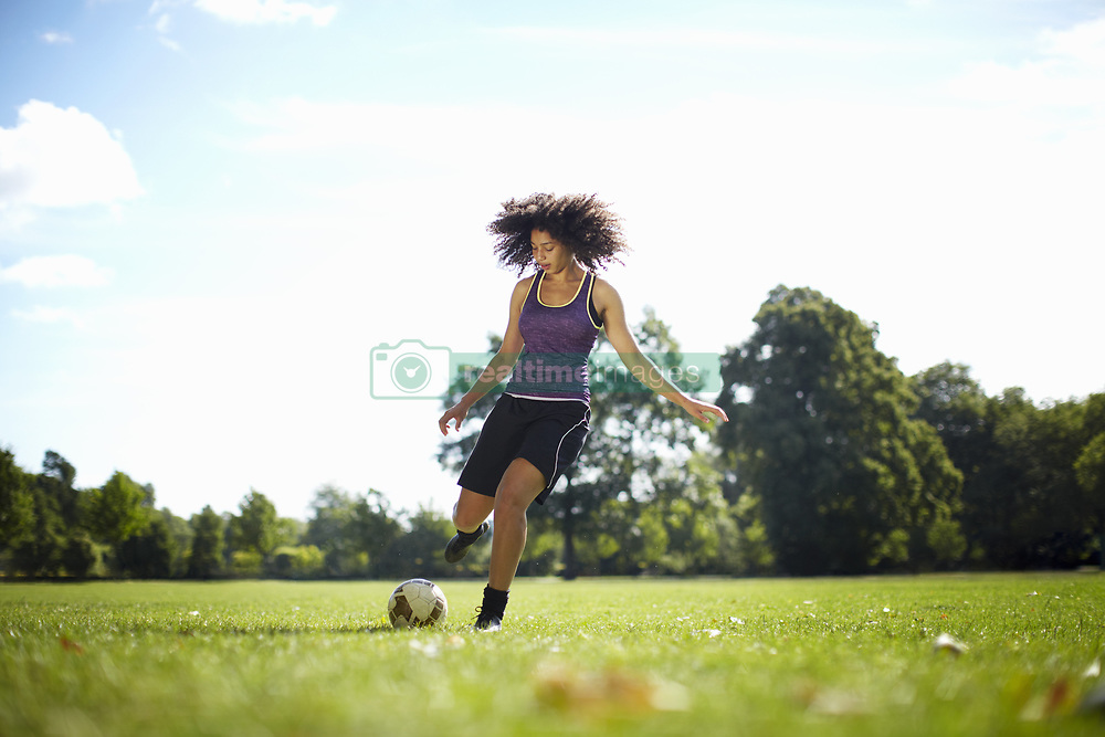 Oct. 15, 2014 - Young woman kicking soccer ball in park (Credit Image: © Image Source/Image Source/ZUMAPRESS.com)