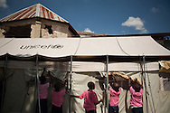 Students roll up window shades on their UNICEF-donated tent classroom at the Saint Gerard School in Port-au-Prince, Haiti, during a visit by a UNICEF delegation, Tuesday, October 12, 2010.  The school was heavily damaged in the January 12 quake.