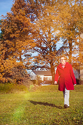 Old woman walking on meadow at park