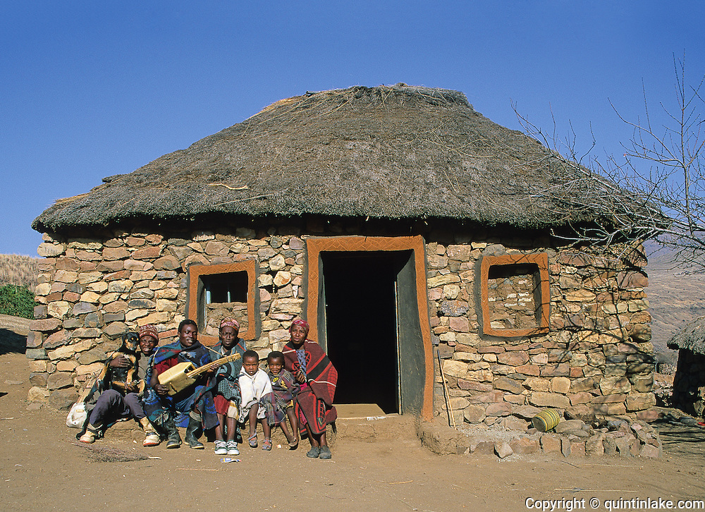 Thabang and family outside their home in Ha Motenalapi in the Senqunyane valley. They are wearing their Basotho tribal blankets. The door and window mouldings demonstrate Litema, the mural art of the Basotho. The hut floor and window mouldings are made from Daga, a mix of earth and dung. The high ammonia content of the dung acts as an antiseptic. The patterns engraved around the doorways may represent the surrounding furrowed fields. Ha Motenalapi, Lesotho, 2000