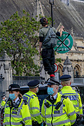 A man defies the police by standing on one of the government-owned vehicles with a stop/go green sign in Parliament Square, central London on Thursday, Sept 10, 2020. This is the last official day of continuous ten days protests to disrupt political institutions throughout peaceful actions swarming central London into a standoff, demanding that central government obeys and delivers Climate Emergency bill. (VXP Photo/ Vudi Xhymshiti)