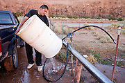 22 OCTOBER 2007 -- MONUMENT VALLEY, UT: AJ RYAN STANLEY, a Navajo Indian living on the Navajo reservation in northern Arizona, rinses out a 50 gallon water barrel before filling it with potable water at the well at Goulding's Trading Post in Monument Valley, UT. Stanley and his grandfather make daily trips to the well for potable water because they don't have a domestic water supply at their homestead. More than 30 percent of the homes on the Navajo Nation, about the size of West Virginia and the largest Indian reservation in the US, don't have indoor plumbing or a regular supply of domestic water. Many of these homes have to either buy water from commercial vendors or haul water from public wells. A Federal study showed that the total cost of hauling water was about $113 per 1,000 gallons. A Phoenix household, in comparison, pays just $5 a month for up to 7,400 gallons of water. The lack of water on the reservation means the Navajo are among the most miserly users of water in the United States. Families that have to buy or haul water use only about 15 gallons of water per day per person. In Phoenix, by comparison, the average water use is about 170 gallons per day.  Photo by Jack Kurtz
