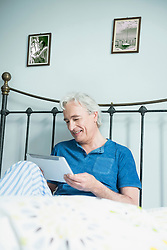 Mature man sitting in bed and using digital tablet, smiling
