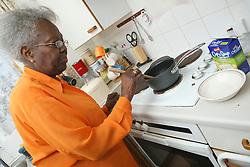 Elderly lady in kitchen.