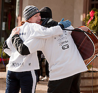 Melissa Guldbrandsen and Paul Warnick exchange an embrace outside of Burrito Me at the conclusion of the Frozen 5K race on Saturday morning.  (Karen Bobotas/for the Laconia Daily Sun)