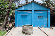 Blue house with a water well and coconut tree..Very modest houses are built on the beach front in An Thoi, south of Phu Quoc Island, Vietnam, Asia 2012