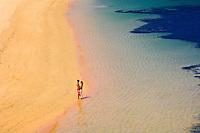 A honeymooning couple stroll a secluded beach, Vatulele Island Resort, Fiji Islands