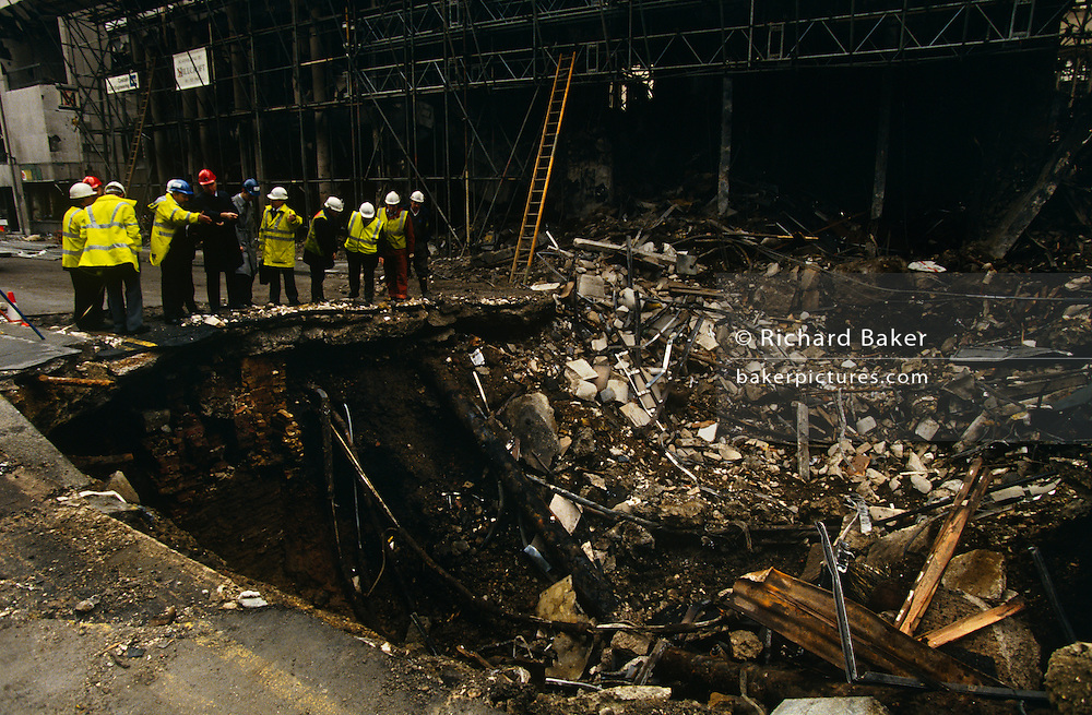Two days after the Irish Republican Army (IRA) exploded a truck bomb on Bishopsgate, a main arterial road that travels north-south through London's financial area, City of London engineering officials examine the huge crater left by the terrorist device. We see debris around the hole with drainage and road material. It was said that Roman remains could be viewed at the bottom of the pit the bomb created. One person was killed when the one ton fertiliser bomb detonated directly outside the medieval St Ethelburga's church. Buildings up to 500 metres away were damaged, with one and a half million square feet (140,000 m²) of office space being affected and over 500 tonnes of glass broken. Costs of repairing the damage was estimated at £350 million. It was possibly the (IRA's) most successful military tactic since the start of the Troubles.