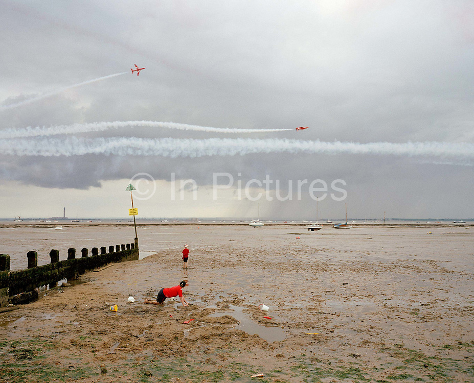 During the annual Southend Air show on the Thames river estuary, two jets of the 'Red Arrows', Britain's Royal Air Force aerobatic team, perform their Corkscrew manoeuvre, a fly-past 100 feet (30m) off the ground. Children playing on the low-tide mud pause from digging holes with a bucket and spade as the aircraft make their way over boating and mudflats. The Red Arrows Hawks perform throughout their calendar of appearances at air shows and fly-pasts across the UK and a few European venues. Since 1965 the squadron have flown over 4,000 shows in 52 countries and are an important part of Britain's summer events where aerobatics aircraft perform their manoeuvres in front of massed crowds.
