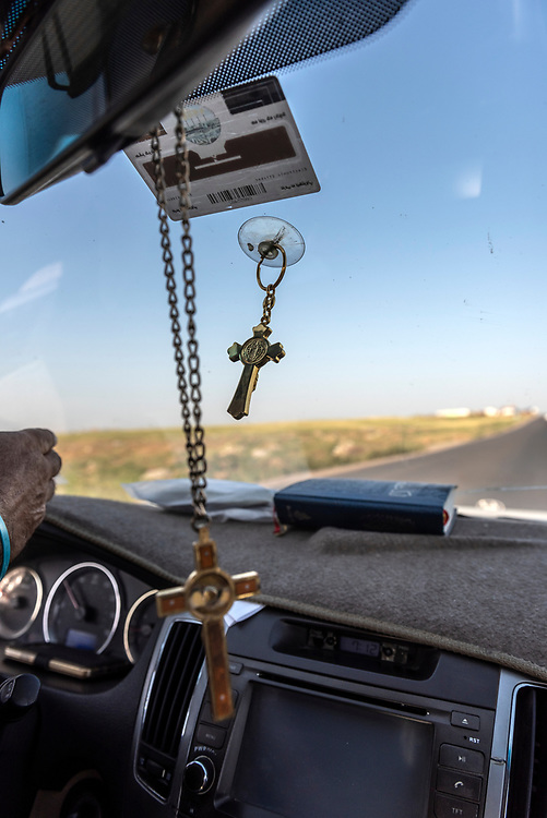 A car driven by an Iraqi Christian travels on the road between Erbil and Mosul, crosses swinging from the rearview mirror and windshield and a Bible on the dashboard. (May 5, 2017)