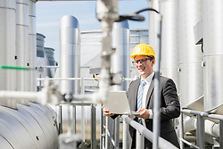 Young businessman working on laptop at geothermal power station, Bavaria, Germany