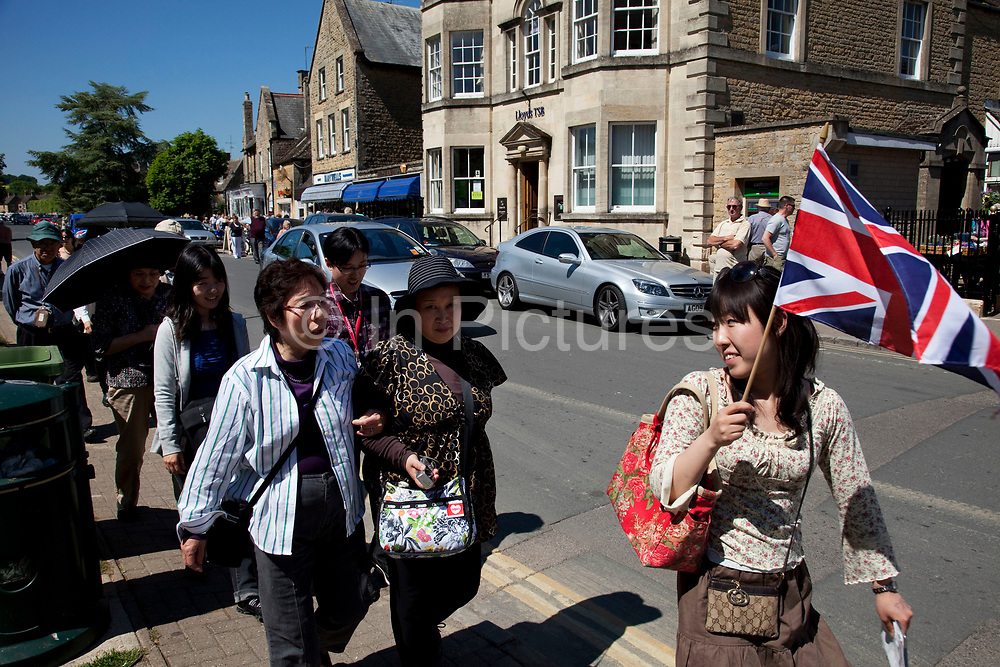 Chinese tourists take a guided tour at Bourton-on-the-Water in The Cotswolds, Gloucestershire, UK.  It is known as the 'Venice of the Cotswolds' because of the bridge-spanned stream that runs through the village, this is one of the most popular places to visit in the area. Popular with both the English themselves and international visitors from all over the world, the area is well known for gentle hillsides 'wolds', outstanding countryside, sleepy ancient limestone villages, historic market towns and for being so 'typically English' where time has stood still for over 300 years. Throughout the Cotswolds stone features in buildings and stone walls act as a common thread in seamlessly blending the historic towns & villages with their surrounding landscape. One of the most 'quintessentially English' and unspoiled regions of England.
