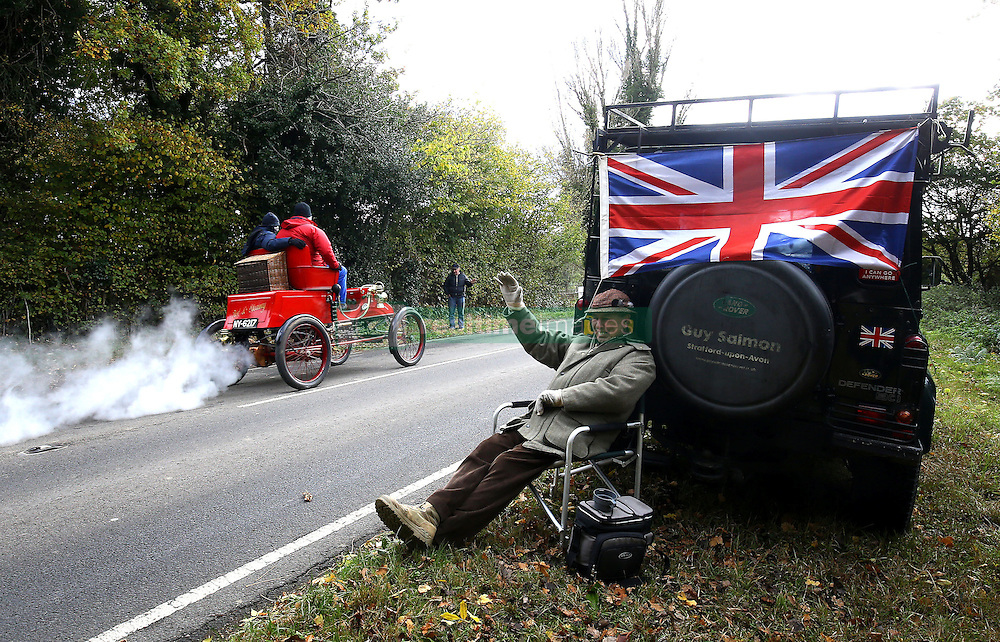 Participants in the Bonhams London to Brighton Veteran Car Run pass a spectator as they head up Holmsted Hill near Crawley, Sussex.