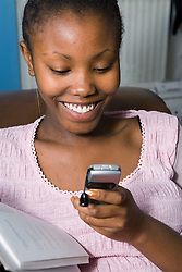 Girl reading text message on mobile phone and smiling,
