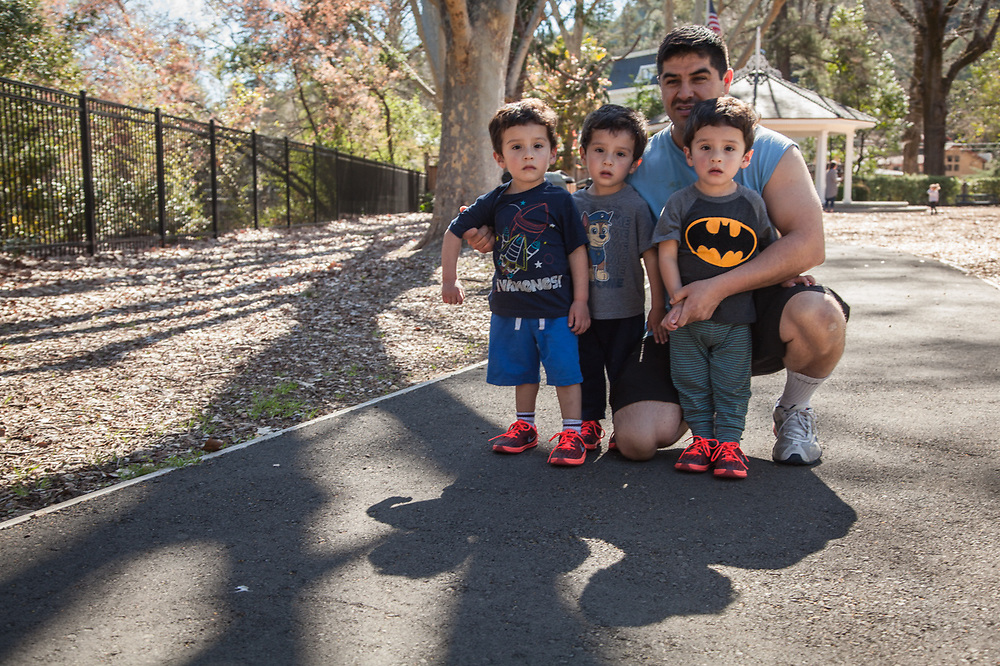 """Winery truck driver Agustin Cendejar with his three two-year old sons Leo, Jullian and Sandro in Calistoga.  """"I work nights and my wife works days...we have our hands full.""""  agustin.cendejar@jfwmail.com"""