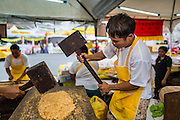 24 SEPTEMBER 2014 - BANGKOK, THAILAND:  Men make Chinese peanut brittle, a popular snack sold during the Vegetarian Festival in Bangkok. The Vegetarian Festival is celebrated throughout Thailand. It is the Thai version of the The Nine Emperor Gods Festival, a nine-day Taoist celebration beginning on the eve of 9th lunar month of the Chinese calendar. During a period of nine days, those who are participating in the festival dress all in white and abstain from eating meat, poultry, seafood, and dairy products. Vendors and proprietors of restaurants indicate that vegetarian food is for sale by putting a yellow flag out with Thai characters for meatless written on it in red.    PHOTO BY JACK KURTZ
