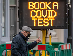 © Licensed to London News Pictures. 04/01/2021. London, UK. Members of the public walk past a 'Book A Covid Test' sign in Fulham, South West London as Downing Street considers putting areas of the UK into Tier 5 restrictions as Prime Minister Boris Jonson ordered schools and primary schools to close in London and parts of the South East. Today, Health Minister Matt Hancock revealed that the government could introduce another full national lockdown as ministers decide how to reduce Covid-19 case numbers from rising further. Photo credit: Alex Lentati/LNP
