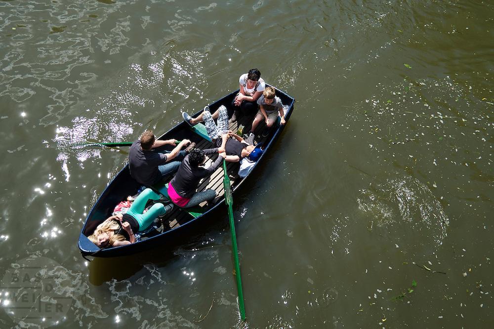 Een gezin vaart in een roeiboot door de grachten van Utrecht. <br /> <br /> A family is boating in the canals of Utrecht.