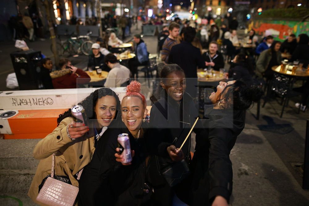 © Licensed to London News Pictures. 12/04/2021. Manchester, UK. People on a night out in Manchester City Centre as government restrictions to control the spread of Coronavirus are eased across the UK. Pubs, restaurants, hairdressers, gyms and non essential retailers are now permitted to serve customers . Photo credit: Joel Goodman/LNP
