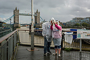 Tourists wearing rain-proof capes from a tour bus company, take a selfie in front of Tower Bridge, on the riverbank near the Tower of London, on 14th September 2017, in London, England.