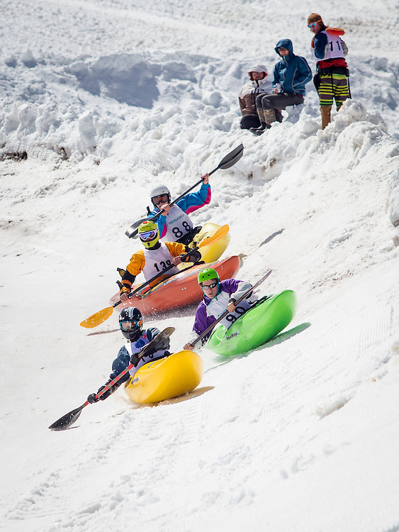 Racers guide kayaks down a snaking snow covered course into a pool of water.