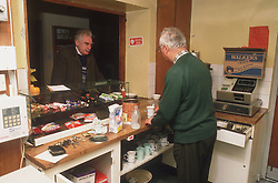 Elderly man serving people through hatch at day centre,