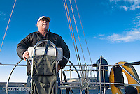 A man steers a sailboat in the San Juan Islands of Washington, USA