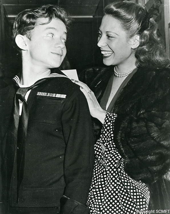 1944 Dinah Shore sign her autograph on the back of a sailor at the Hollywood Canteen.
