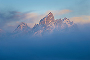 The Grand Teton emerges from the fog at sunrise after a summer storm in Grand Teton National Park, Jackson Hole, Wyoming