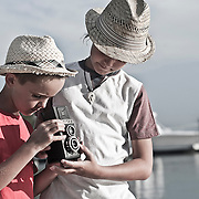 Two young photographers playing with a vintage, viewfinder film camera in an exotic location.