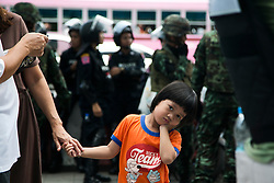© Licensed to London News Pictures. 24/05/2014. A young girl holds onto her mothers hand in front of Thai military and riot police following a Anti-Coup protest in Bangkok Thailand. The Royal Thai army announced a Military coup and have imposed a 10pm curfew.  Photo credit : Asanka Brendon Ratnayake/LNP