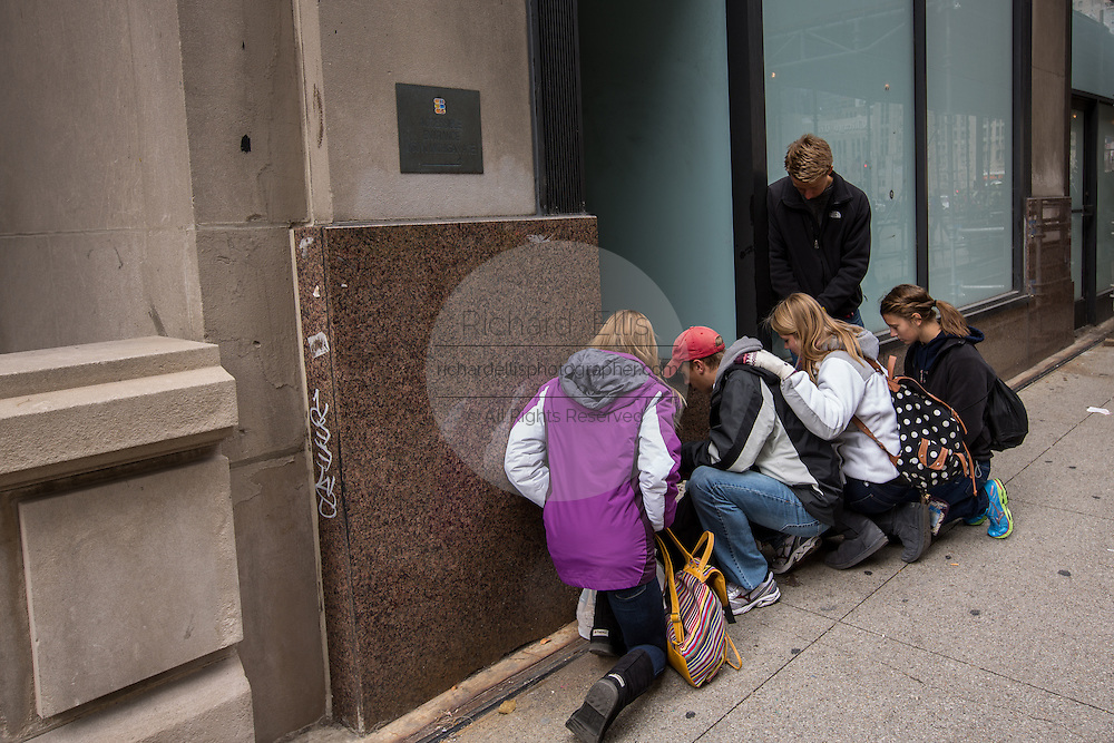 Young evangelists pray over a homeless man along South Michigan Avenue in Chicago, IL.