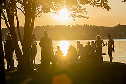 Group of young friends partying at lakeside during sunset, Bavaria, Germany