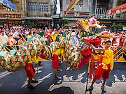 """19 FEBRUARY 2015 - BANGKOK, THAILAND: Chinese dragon dancers wait to perform for Chinese New Year at a business on Yaowarat Road in Bangkok. 2015 is the Year of Goat in the Chinese zodiac. The Goat is the eighth sign in Chinese astrology and """"8"""" is considered to be a lucky number. It symbolizes wisdom, fortune and prosperity. Ethnic Chinese make up nearly 15% of the Thai population. Chinese New Year (also called Tet or Lunar New Year) is widely celebrated in Thailand, especially in urban areas that have large Chinese populations.    PHOTO BY JACK KURTZ"""