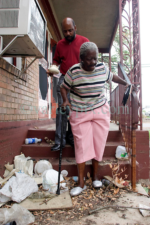 07 Oct, 2005.  New Orleans, Louisiana. Hurricane Katrina aftermath.<br /> 81 year old Rosella McKoy steps over trash washed in by the floods as she leaves her home in the projects with a few precious belongings. Her nephew, Kerry Young (41yrs) gave her a ride back from Baton Rouge to check out her home in New Orleans.<br /> Photo; ©Charlie Varley/varleypix.com