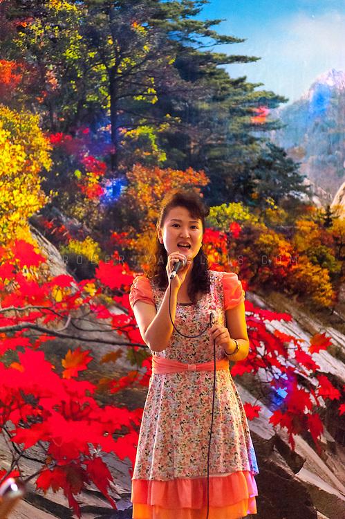 Waitress performing Karaoke songs against a painted landscape backdrop, Pyongyang, DPRK (North Korea)