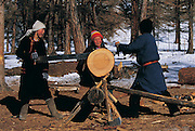 Children sawing logs<br /> near Lake Hovskol<br /> Mongolia<br /> Winter