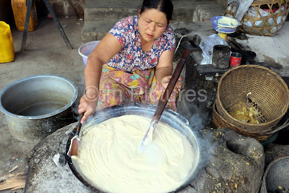 An Intha woman stirs a pan of tofu over a fire on 22nd January 2016 in Shan State, Myanmar. Located on the northwestern shore of Inle Lake, the Intha village of Kaung Daing is known for its tofu, prepared using split yellow peas instead of  soybeans