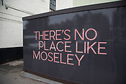 Street scene of a new development hoarding in Moseley, Birmingham, United Kingdom. Moseley is known as one of the more up market neighbourhoods in Birmingham, but still shows signs of downturn, and lack of consistent investment and general upkeep away from the residential areas, like here on Moseley Road.