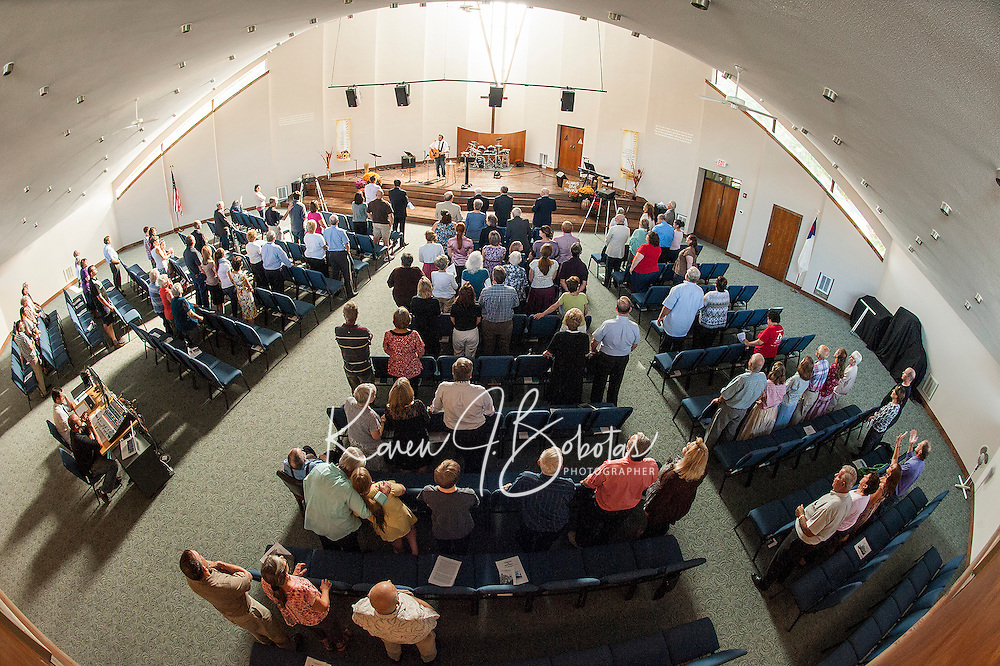 """Pastor Dan Lyle joins parishoners and guests in an opening song """"10,000 Reasons to begin the Evangelical Baptist Church dedication ceremony Sunday afternoon.  (Karen Bobotas/for the Laconia Daily Sun)"""