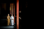 Two monks look on in a courtyard wooden room during their visit to the Yonghe Temple (Chinese 雍和宮, pinyin Yōng hé gōng), also known as the Lama Temple in Beijing, China, August 15, 2014.<br /> <br /> Confucianism, Taoism and Buddhism are the three major religions in China. Temples and statues witness their ancient roots all over the Chinese country.<br /> <br /> © Giorgio Perottino