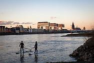 view over the Rhine to the Kranhaeuser (Crane Houses) in the Rheinau harbour and the cathedral, stand-up-paddler, Cologne, Germany.<br /> <br /> Blick ueber den Rhein zu den Kranhaeusern im Rheinauhafen und zum Dom, Stand-Up-Paddler, Koeln, Deutschland.