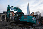 Construction area being cleared by workmen in two diggers on a demolition site in view of The Shard in Southwark, London, England, United Kingdom.