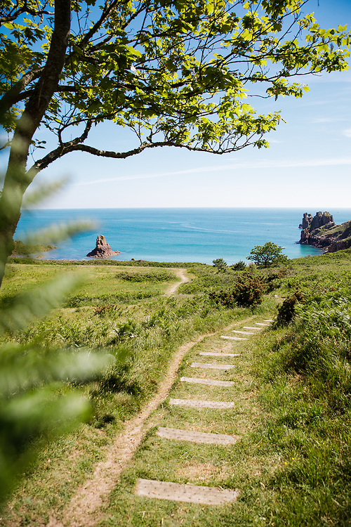 Path winding through the grass down to Beauport beach, with its calm, turquoise water on a sunny day in summer in Jersey, Channel Islands