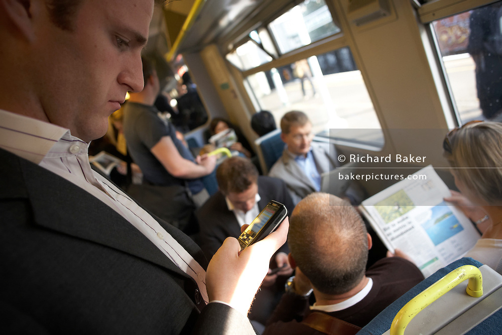 Rush hour train commuter checks messages on-board carriages travelling into city mainline stations in south London.