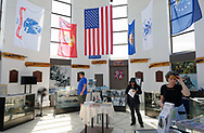 East Meadow, New York, USA. May 25, 2019. Visitors at the Nassau County Veterans Memorial Museum look at miliary memorabilia displayed under the American Flag and military flags of the United States Armed Forces - Army, Navy, Marine Corps, Air Force, Coast Guard - suspended high in the ceiling, during Saturday of Memorial Day Weekend at Eisenhower Park on Long Island.