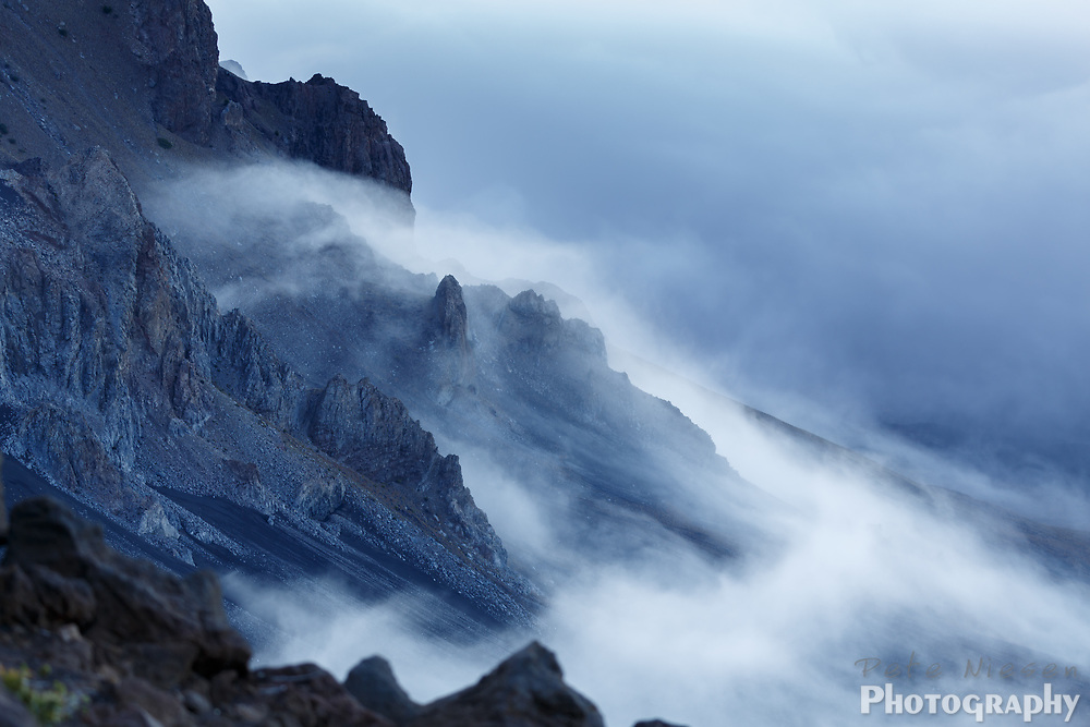 Mist and fog pass over rugged steep and jagged volcanic mountain landscape