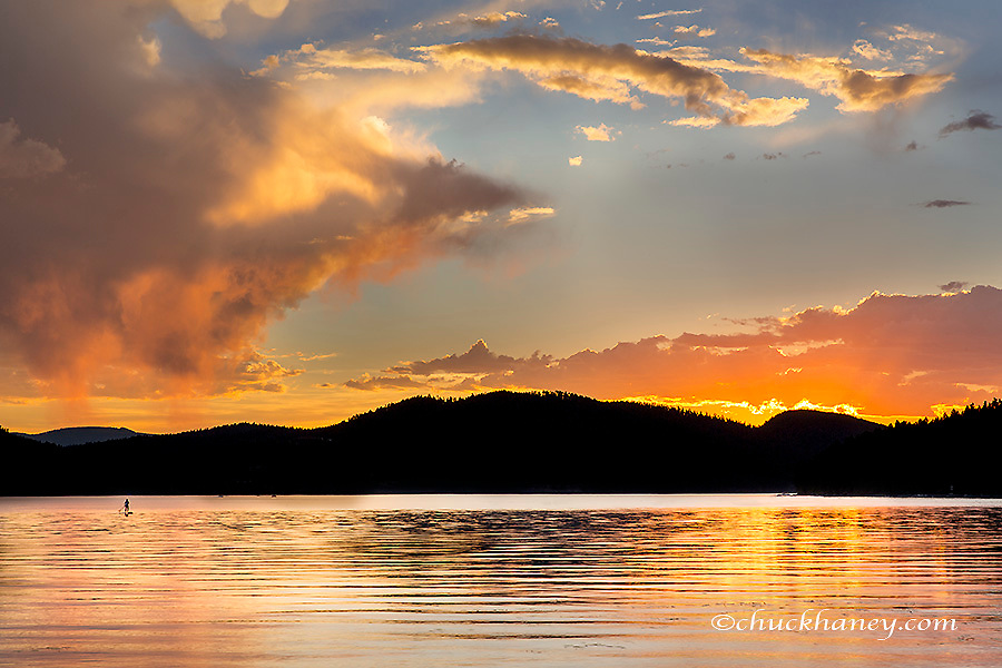 Standup paddleboarder silhoutted by beautiful sunset clouds on Whitefish Lake in Whitefish, Montana, USA